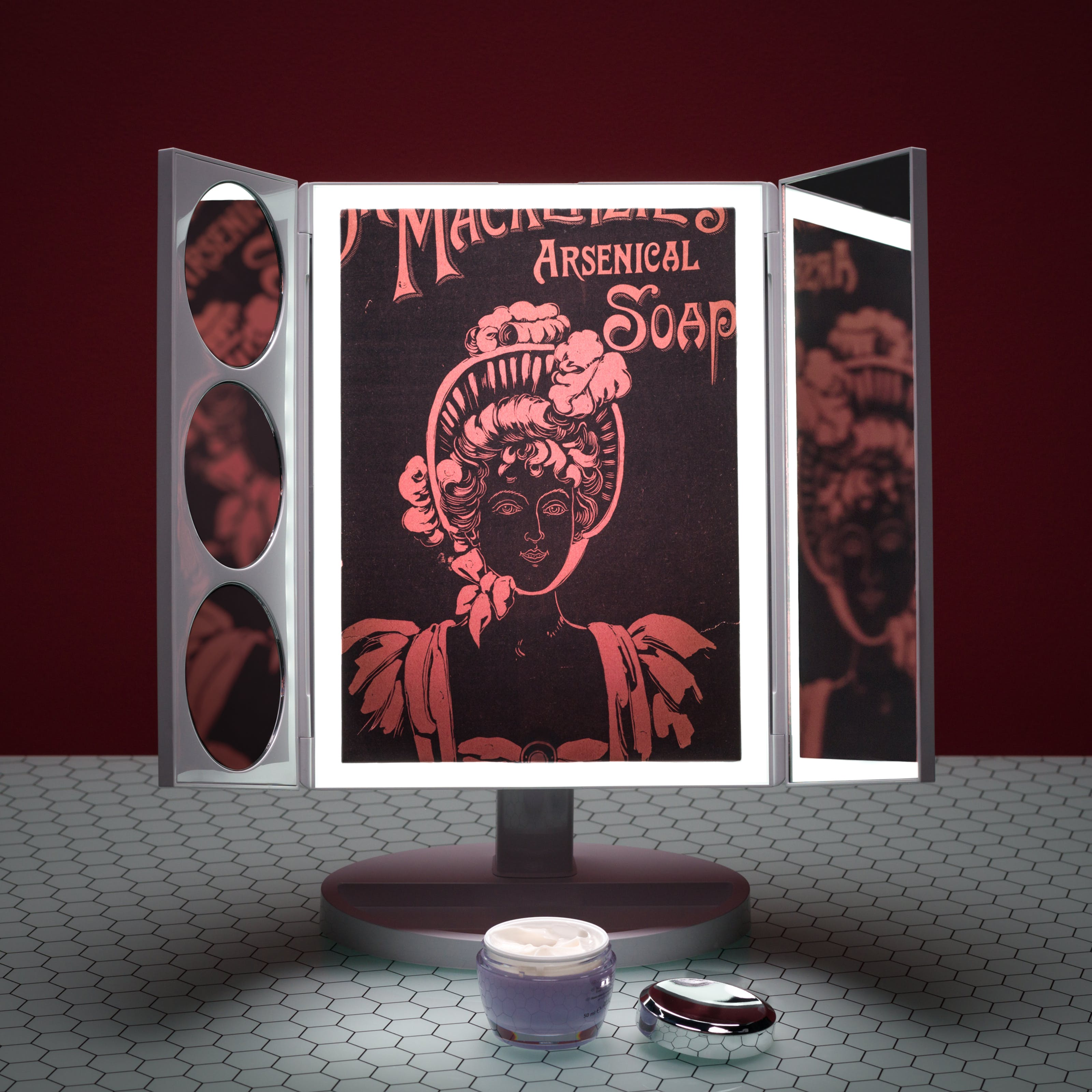 Photograph of a three-fold table beauty mirror with built-in light on a glass patterned tabletop, against a dark red background. On the table in front of the mirror is an open jar of face cream. In the reflections of the mirror an old advertisement for Dr. Mackenzie's Arsenical Soap, be seen.