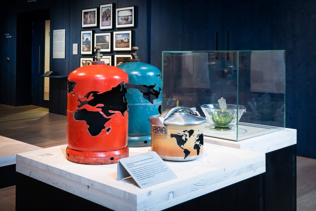 Photograph of an artwork on a display plinth in a gallery space. The artwork consists of 2 gas canisters and a pressure cooker, each one has a map of the earth