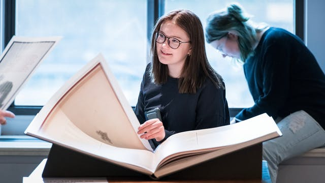 Photograph of a young women looking at a large facsimile book whilst researching in the Reading Room at Wellcome Collection.