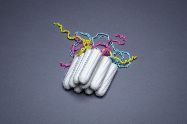 Photograph of a stack of unwrapped tampons against a blue background. The yellow, pink and blue cords are visible behind the stack.
