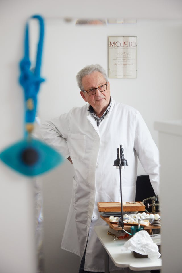 Photograph of an older man wearing a white lab coat in the reflection of a mirror He is standing at a workbench with covered in tools and glass eyes, with his hand on his hip, looking off into the distance. Hung on the corner of the mirror is a blue eye on a blue cord.