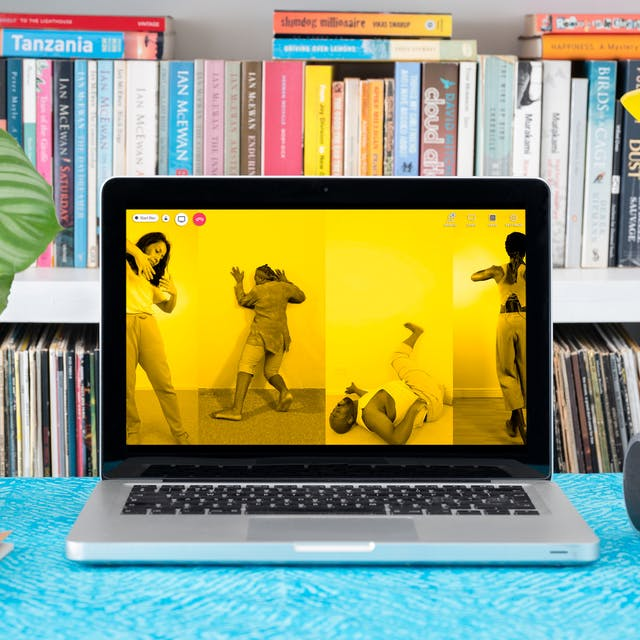 Photograph of a laptop on a desk.  On the laptop screen are four vertical photographs placed side to side, each monotone, but with a bright yellow tone overlaid. Each image shows an individual in a performative pose. On the far left a woman facing the camera just appears into view holding her arm up bent at the elbow, fingers splayed, one hand almost touching the other. The image to right of this one shows a man facing away from the camera hands pushing against a plain wall, leaning hard against it. The image to the right of this shows a man lying on his back on the floor, neck arched back with one foot raised against a plain wall. The image on the far right show a woman just disappearing out of the frame, facing away from the camera. She is standing with her legs crossed and her left arm raised level with her shoulders and bent at the elbow. On the laptop screen are videocall icons, and a red telephone icon. Around the laptop is a houseplant, lamp and headphones.