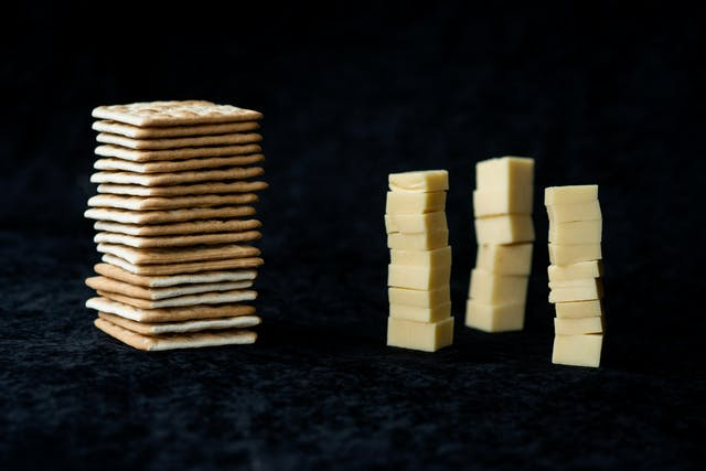 Photograph of a pile of cheese crackers on the left and three towers of cubed cheese on the right. The background is a black velvet material.