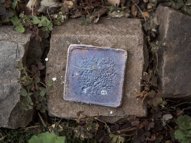 Photograph of a lead plate cooling on a stone.  The lead shows signs of lead oxide on the surface, giving off blue and purple colouring.