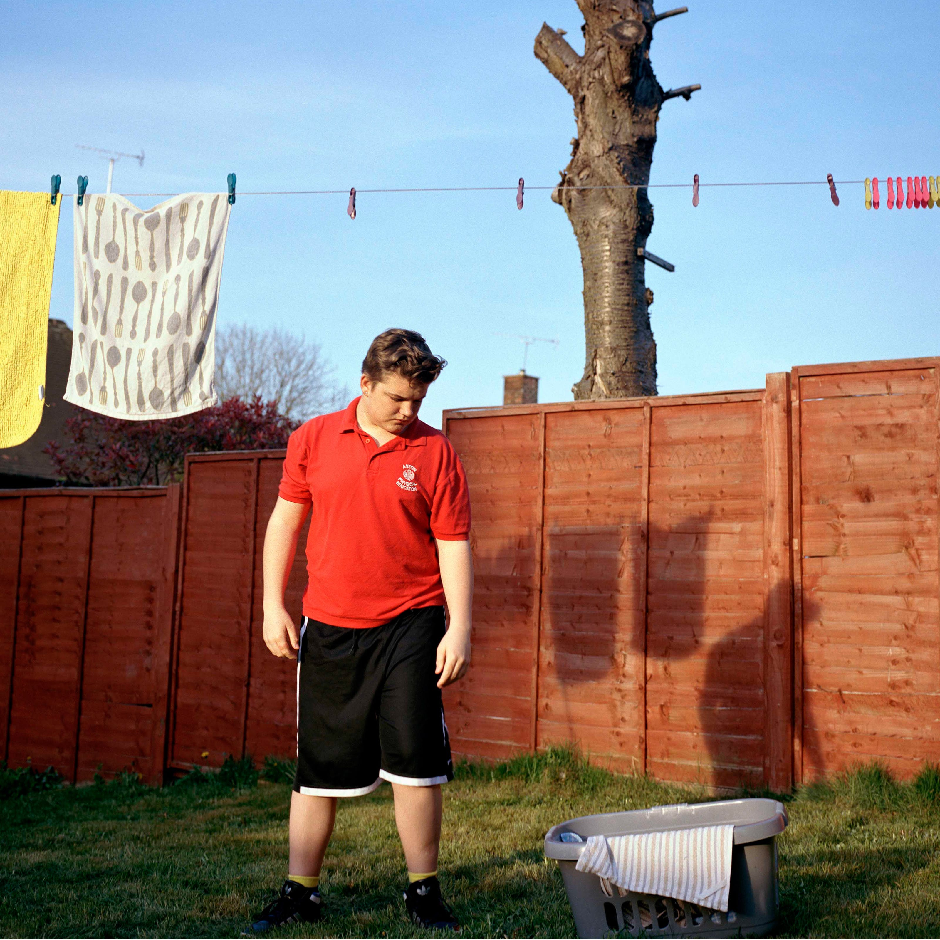 Photograph of a teenage boy wearing a red t-shirt and black shorts, standing in a garden. Above him is a washing line with pegs and towels.