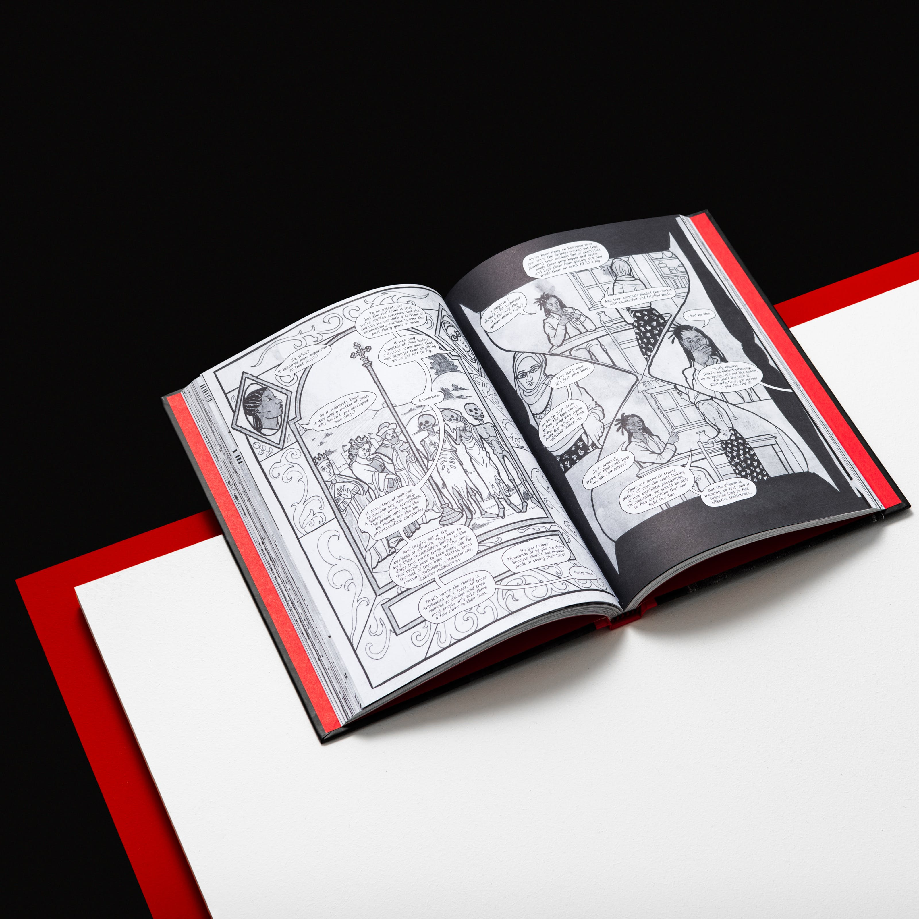 Photograph of an open hardback book resting on a white surface. The top part of the book is overhanging the white surface. Just below the white surface is another red surface creating an edge around the white top. This red compliments the red colour of the inside of the hardback cover. The two open pages of the book show black and white graphic novel illustrations. Behind the book and the surfaces is a black background.