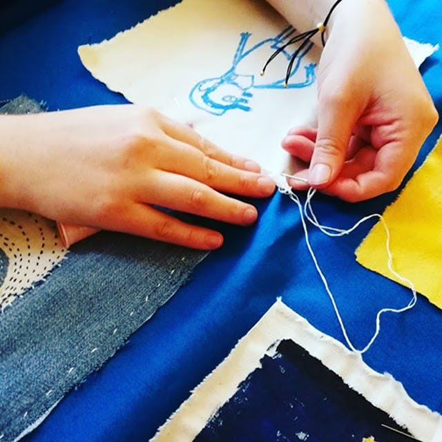 A pair of hands sewing paintings on material squares onto a blue backing cloth.