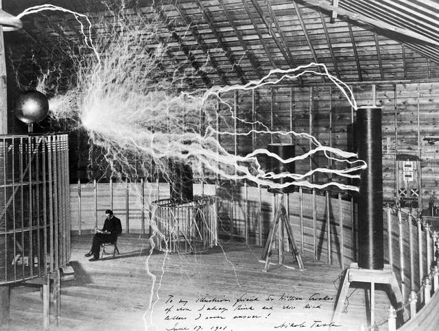 Black and white photograph of electricity arcing across a room with Nikola Tesla sitting in the background
