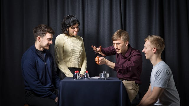 Photograph of a young woman and two young men gathered around a table, working with a magician to learn magic tricks. behind them is a grey curtain and on the table are magic props, such as cup and balls and a deck of playing cards.