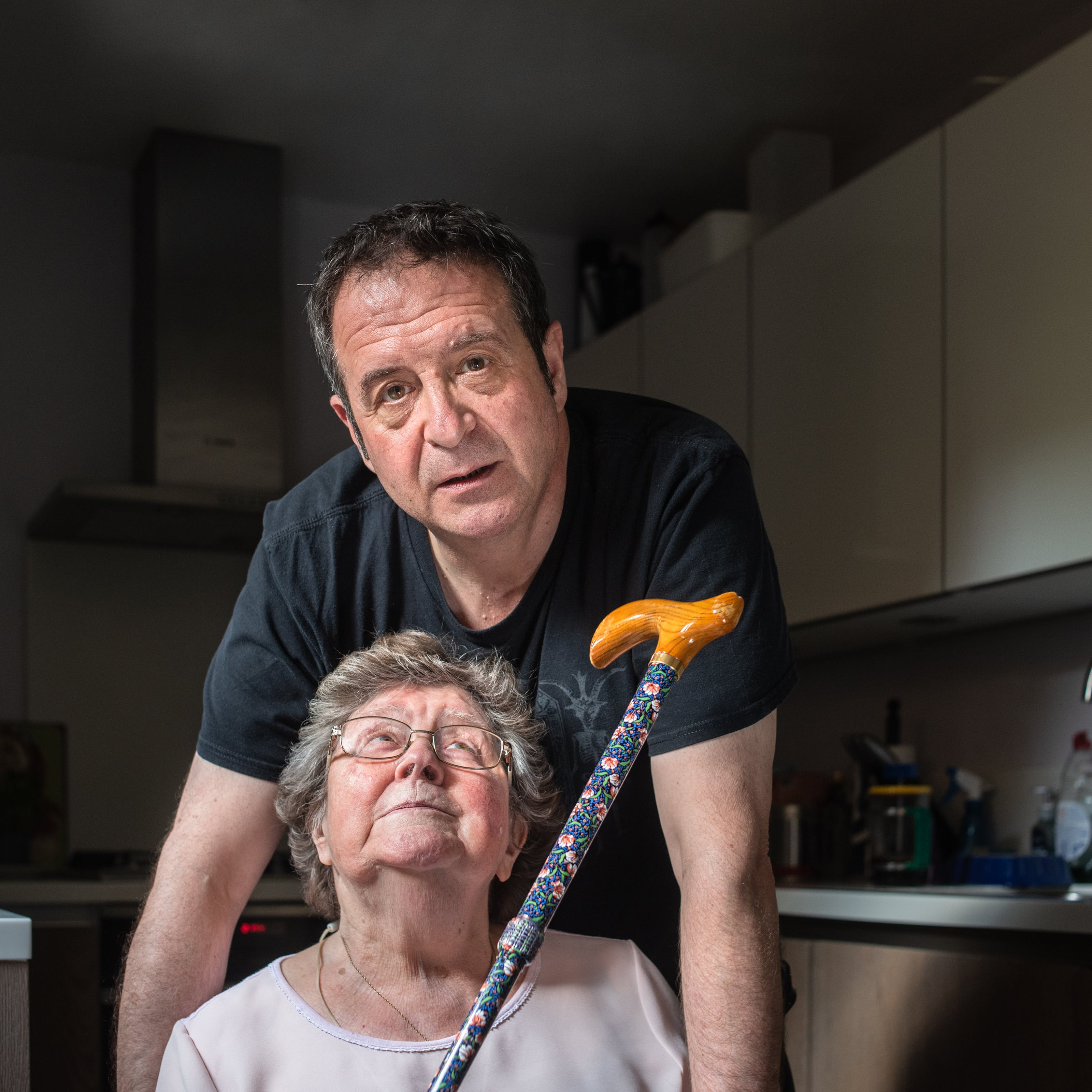 Photograph of a man and his mother in a kitchen. The man wearing a black t-shirt is stood behind his mother who is sitting on a chair. The man is looking straight to camera, leaning slightly forward, his arms resting on the arms of the chair which are out of shot. His mother is wearing a pink blouse and is looking vertically upwards towards him. She is holding her walking stick up towards him, handle end first. In the background are kitchen units, a Tupperware box of biscuits and the tap of the sink.