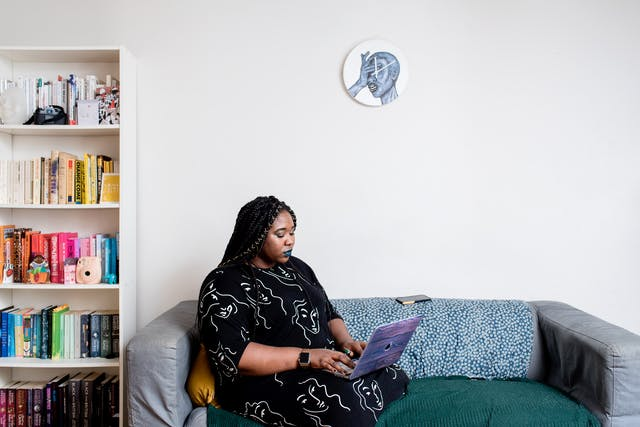 Photograph of a woman inside a house, sitting on a sofa, typing on a laptop computer. To the left is a bookshelf with books on every shelf. Hung on the wall behind her is a clock with an illustration of a face with a hand clasped over the eyes, the mouth slightly open.