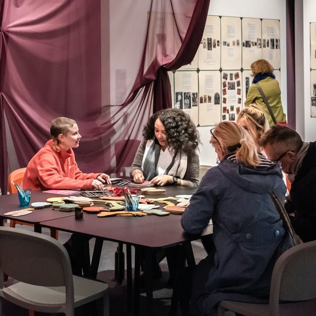 A group of people in conversation around a table in the Misbehaving Bodies exhibition at Wellcome Collection