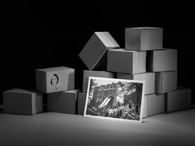Photograph of a set-built scene made up of a grey card horizontal base against a black vertical background. Built into a mock wall are many rectangular brick blocks also made out of grey card. The bricks are stacked together in an untidy pile. Leaning up against the brick wall is a photographic print showing the destruction of London in the Blitz. Stencilled onto the side of one of the boxes is a portrait of a young woman with short hair.