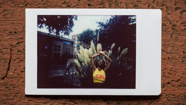 Photograph of an Instax Mini instant film print resting on a textured brick surface.  The print shows a woman standing against the branches and leaves of trees and shrubs outside a street scene and a row of buildings. She has her arms raised up above her head to show her armpit hair. She is wearing a yellow crop top with the words
