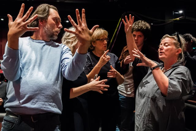 Photograph of a group of people rehearsing. In the foreground to the left of the frame a man with his body facing the camera, his arms out before him and palms facing inwards, his fingers outstretched in a dramatic fashion.  He is looking over his left shoulder towards a woman who has her arms out before her, as if explaining what his movements should be.  Behind them is another group of people who are listening to the instruction.
