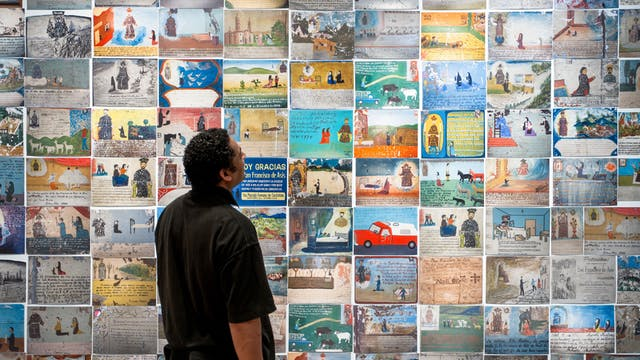 Photograph of a man looking at a wall of colourful Mexican votives, part of the exhibition Infinitas Gracias: Mexican miracle paintings at Wellcome Collection.