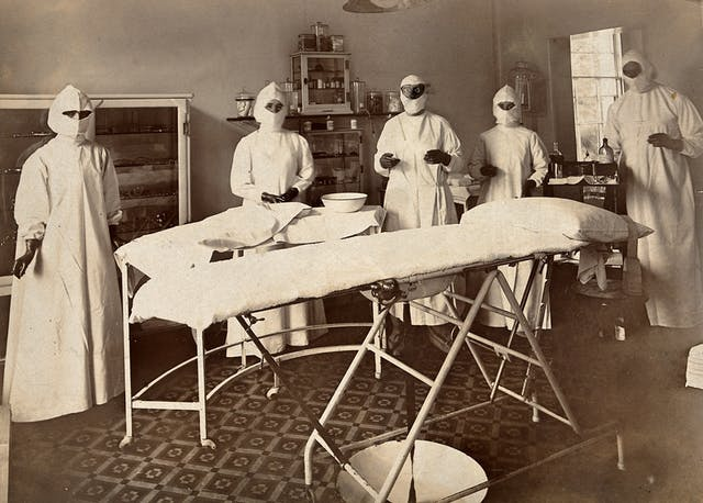 Photograph of operating theatre staff wearing white gowns, mouth-masks, and rubber gloves at Wotton Lodge, Gloucester around 1909.