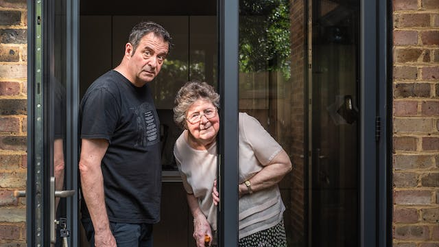 Photograph of a man standing in a glass patio doorway with his mother, both are looking to camera. One of the doors is open. The man is slightly hunched forwards, eyebrows raised causing his brow to furrow. He looks a little