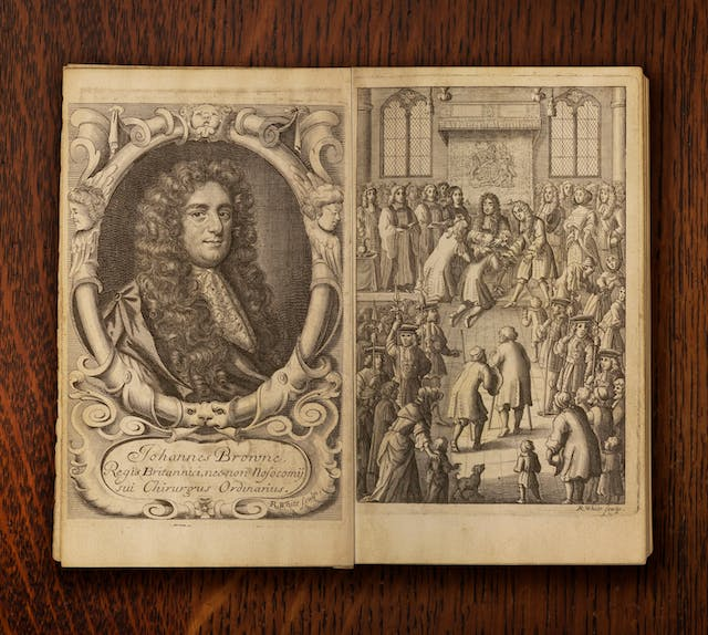 A photograph of an open book against a dark wood background. The pages of the book show two illustrations. To the left is a portrait of Johannes Brown shown with long curly hair and a lace neckerchief. To the right there is a depiction of a crowded official ceremony with the King presented with diseased men who are kneeling in front of him.