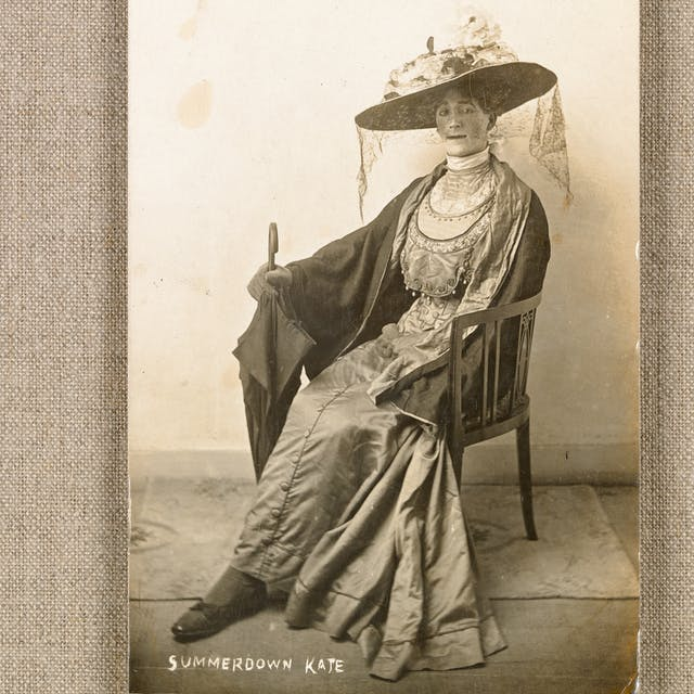 Black and white photograph of a portrait postcard of a seated man in a dress, wearing a large hat with floral decoration. He is holding and umbrella in his right hand. The bottom of the postcard is inscribed with the words,