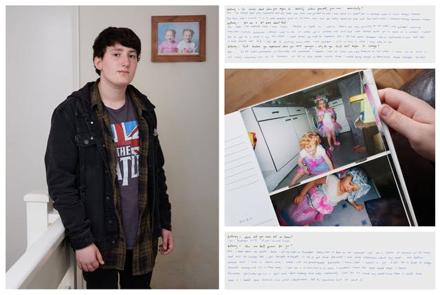 Photograph of an individual standing in an upstairs landing. They are looking straight to camera and behind them on the wall is a framed photograph showing 2 toddlers. To the right of this photograph is another photograph showing a hand holding a family photo of two toddlers in pink and blue outfits. Above and below this image are images of handwritten texts.