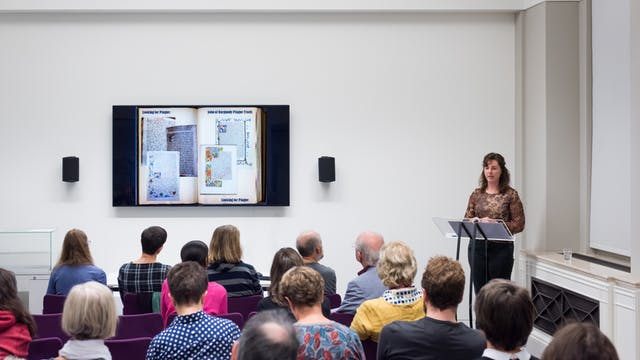 Photograph showing a woman giving a talk in the Viewing Room at Wellcome Collection. She is stood at the front of the room looking at a wall mounted television screen. In the foreground are the backs of the heads of the audience.