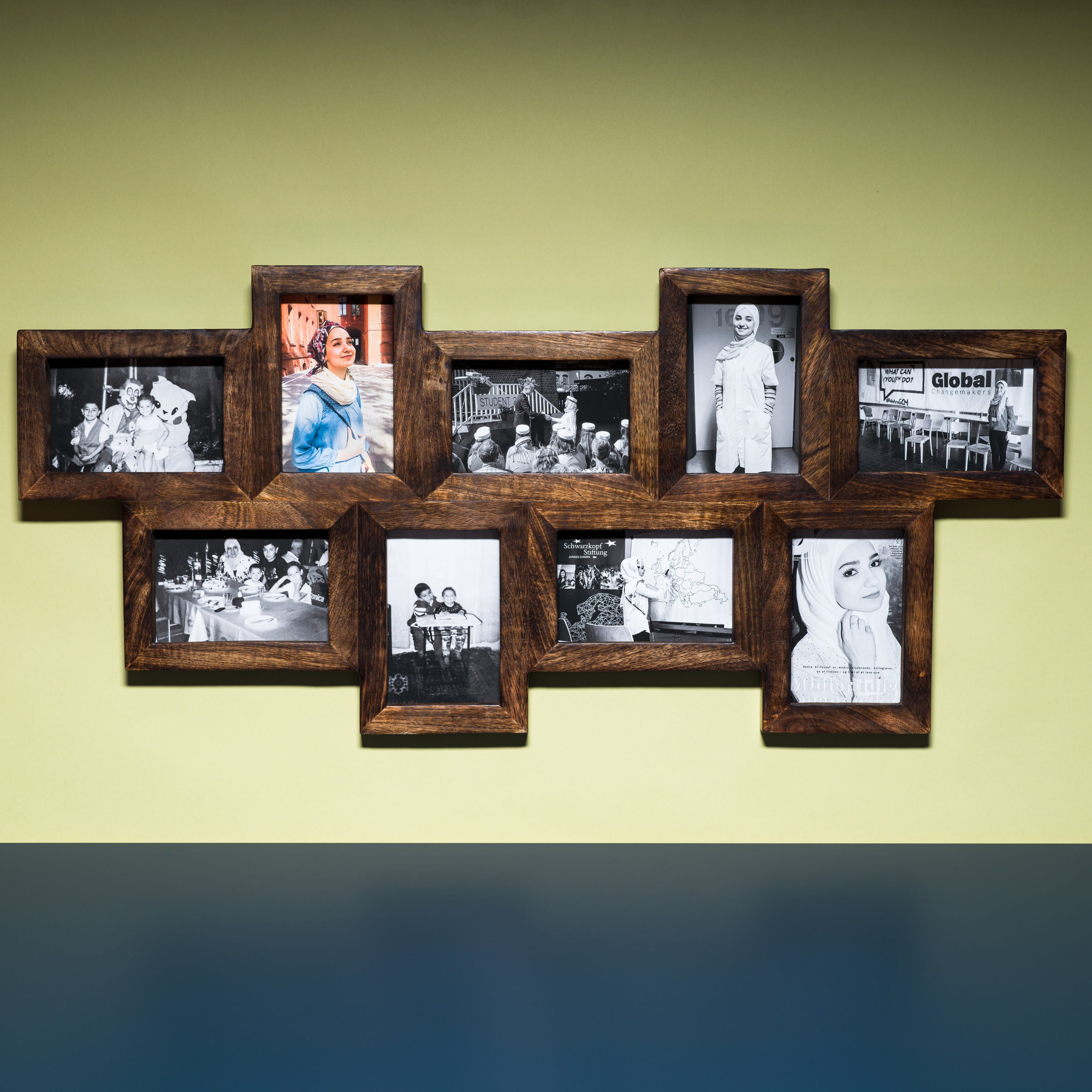 Photograph of a multi-frame photo frame containing nine photographs, eight in colour and one in black and white. The frame is hung on a light green coloured wall above a blue tabletop.