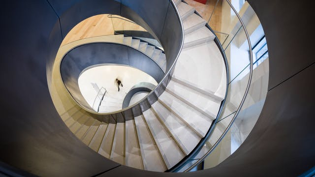 Photograph looking from up high down the centre of an irregular spiral staircase. The sides of the staircase are grey metal with cream stone steps. In the distance on the ground floor of the staircase is a small dark blurred figure about to start climbing the stairs.