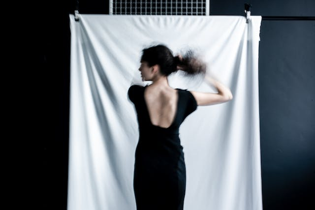 Photograph of a young woman from behind, from the thigh up. Her head is turned to the left revealing her profile. She is wearing a low cut black dress and is in the process of tying her hair. The long exposure of the camera has captured her movement. In the background is a drape of white fabric.