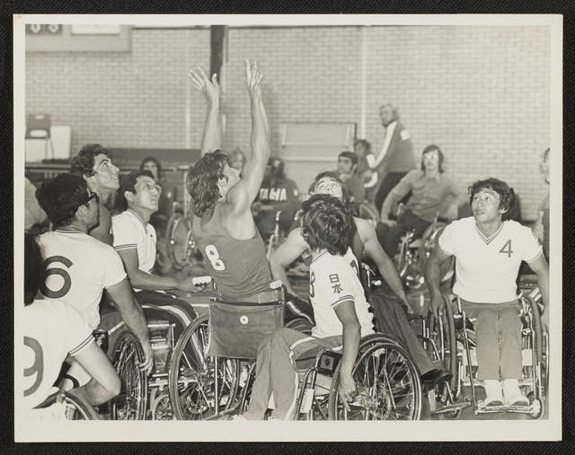 Black and white photographic print showing a wheelchair basketball match. Lots of players are clustered close together in the photograph, looking up into the air. In the centre, a man wearing a dark number 8 shirt has his arms flung upwards as though he has just released the ball for a shot at the net. In the background, spectators seated in front of the brickwork walls look towards the action.