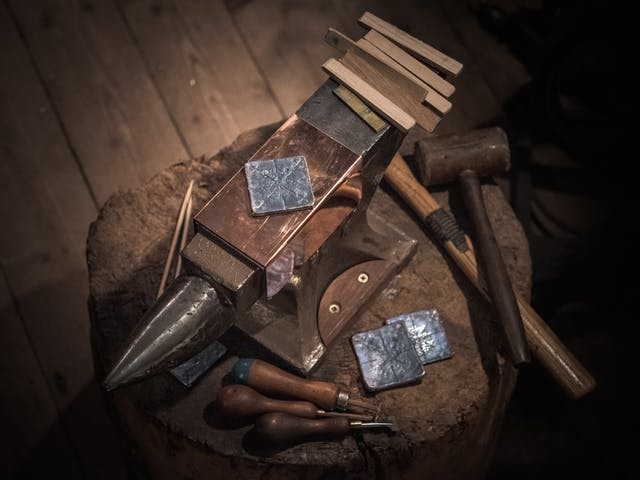 Photograph of a lead plate resting on an anvil.  Surrounding the lead, to the right, are the tools with which the impressions are made, including specially crafted wooden sticks and a wooden mallet.