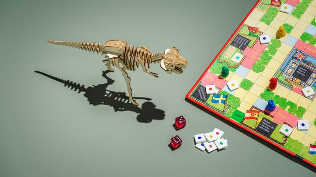 Photograph of a board game placed to the left of the frame,  featuring museums from various countries, red, green, blue and yellow counters, and two red dice.  In the centre of the frame is a laser cut wooden tyrannosaurus rex model.