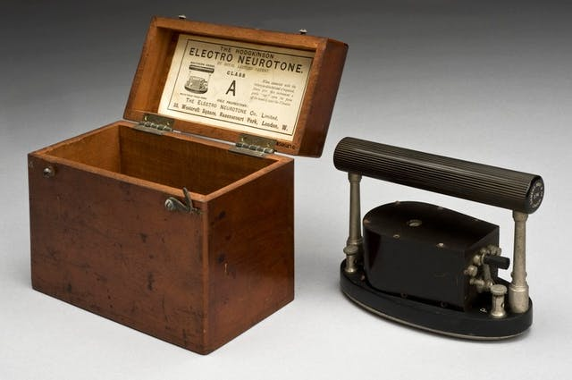 Image of a wooden box next to a black oval piece of metal with a handle on it.