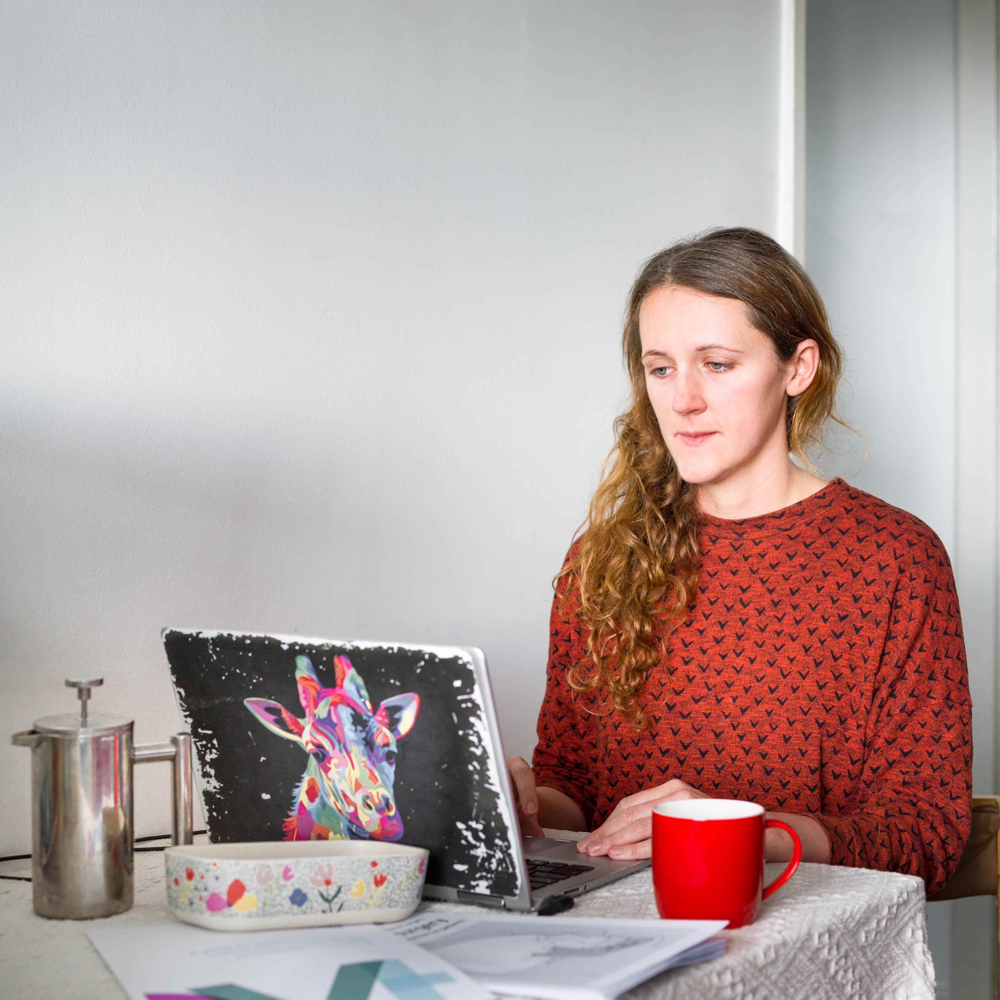"""一个女人坐在餐桌旁靠着白墙的照片,背景是家庭环境。她低头看着桌上打开的笔记本电脑屏幕。在打字过程中,她的手放在键盘上。她穿着一件铁锈色的上衣,上面覆盖着黑色的小""""v""""形,看起来像是在飞翔的鸟儿。她卷曲的棕色头发披散在右肩上。她面前的桌子上放着一块白色的桌布,上面放着一个红色的咖啡杯、一个银色的咖啡杯、一个花盘和打印的A4材质。她的笔记本电脑盖上有一张彩色的长颈鹿头像。"""