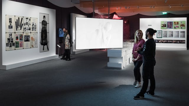 Photograph of the Misbehaving Bodies exhibition at Wellcome Collection, showing a wide view of the space. in the foreground a young man and woman discuss a video piece projected onto a large screen. In the background an other young man and woman look at the artworks that are displayed on the wall.