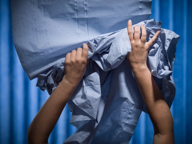 Photograph of a pair of hands struggling to contain a ream of medical blue examination couch paper. Photographed against a background of blue antibacterial clinical curtains.