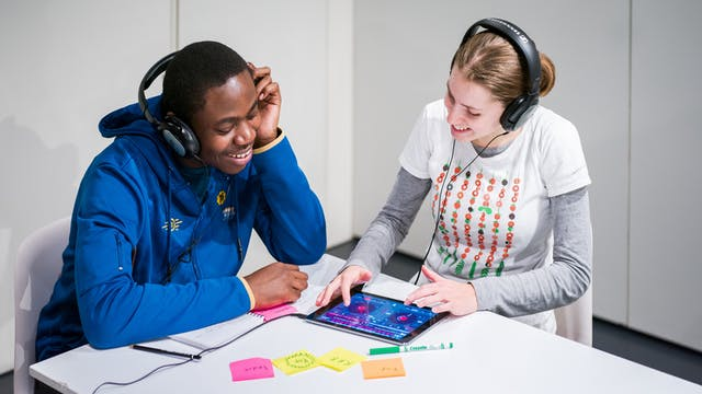 Photograph of a young woman and man sat at a table using a tablet device to create music as part of a Saturday Studio workshop at Wellcome Collection..