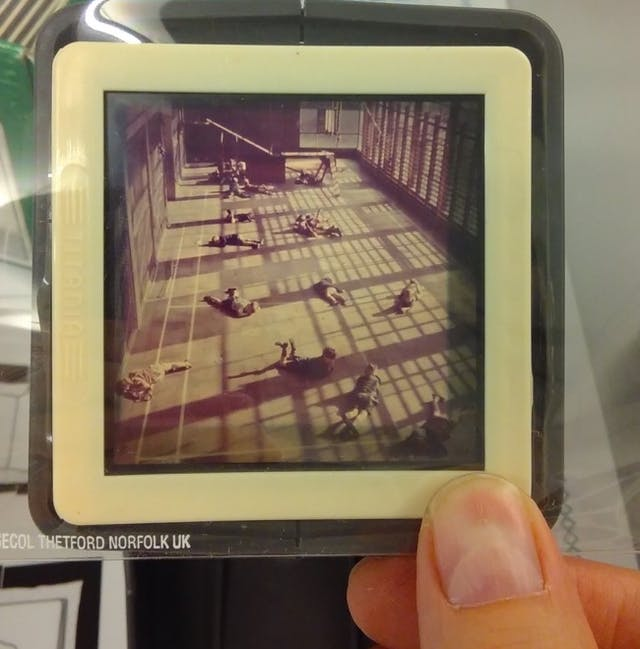 A close-up photo of someone holding a black and white slide between forefinger and thumb; the slide shows people lying on the floor of a large room or gymnasium.