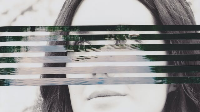 Mixed media collage artwork using a combination of two different photographic prints. The background of the collage is made up of a black and white photograph of the head of a young woman with long dark hair. She is looking off to camera left with a neutral expression on her face. Overlaid on top of her portrait, running through the centre of the image, are horizontal strips of a colour photograph showing a large expanse of open water with the ripples on the surface of the water visible through the light and dark reflections. The horizontal strips are spaced out such that the portrait beneath can be seen through the gaps.