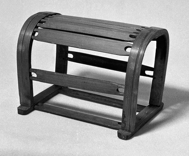 Black and white photograph of a wooden pillow, which looks like half a barrel with some of the wood missing.