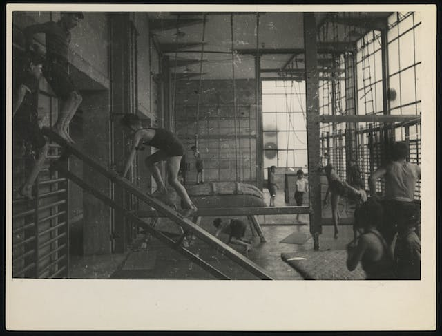 Black and white photograph showing boys and young men exercising in a gymnasium.