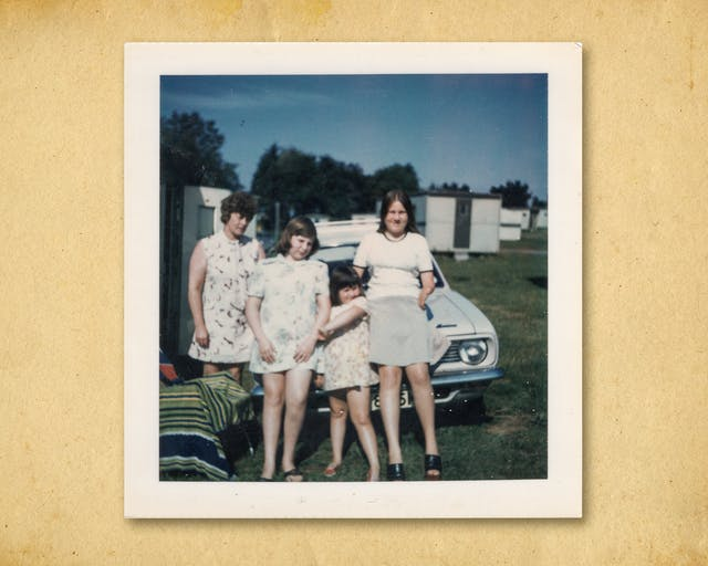 Photograph of a colour photographic print, resting on a brown paper textured background. The print shows a family of 3 daughters and their mother outside on a caravan site. They are leaning on the bonnet of their car, looking to camera, squinting slightly into the sun.