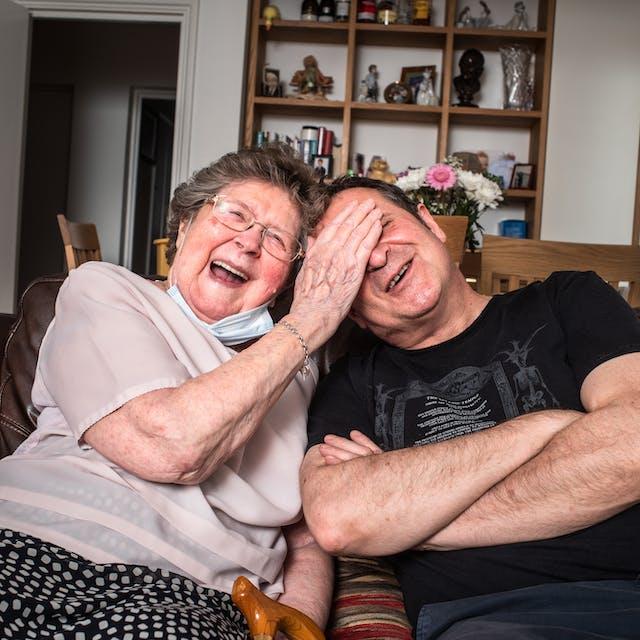 一个男人和他的母亲的照片在一个沙发坐在一个在客厅的一张沙发。那个男人坐在右边,双臂交叉。他倾向于他的母亲。他的母亲坐在左边笑着大声笑着朝着她的儿子倾斜,把右手放在他的眼睛和额头上。在背景中是一个包含书籍,饰品,烈酒和家庭照片的搁架单元。