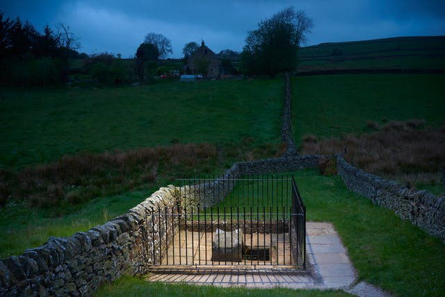 Photograph at dusk of a fenced off well, surrounded by dry stone walls and fields. IN the distance is a remote farm house on a hill. The well is spotlit.