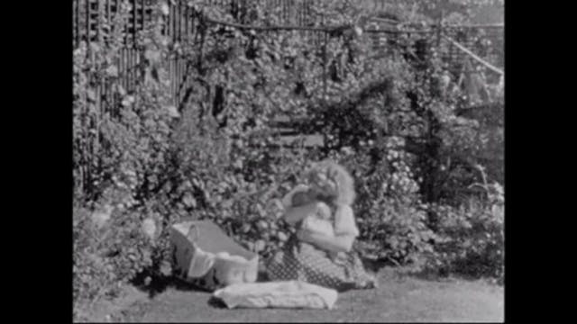 Image of a woman holding a baby in a garden.