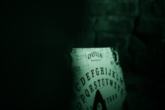Photograph of a ouija board in a dark brick alcove. The image is toned green as a result of being made under infrared light.