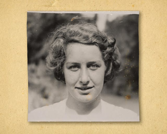 Photograph of a black and white photographic print, resting on a brown paper textured background. The print shows the head and shoulders of a woman outside in a garden. She is looking to camera, wearing a white shirt.