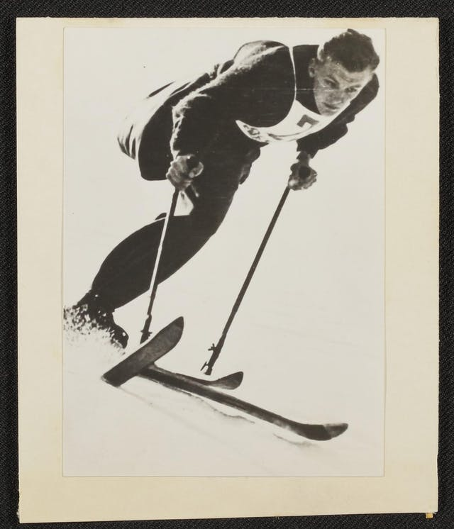 Black and white photographic print of a man skiing. He has one leg and one stump. He leans forward, gripping his poles, and snow sprays up from under his ski, indicating speed. His expression indicates concentration as he gazes off toward the bottom right of the image.