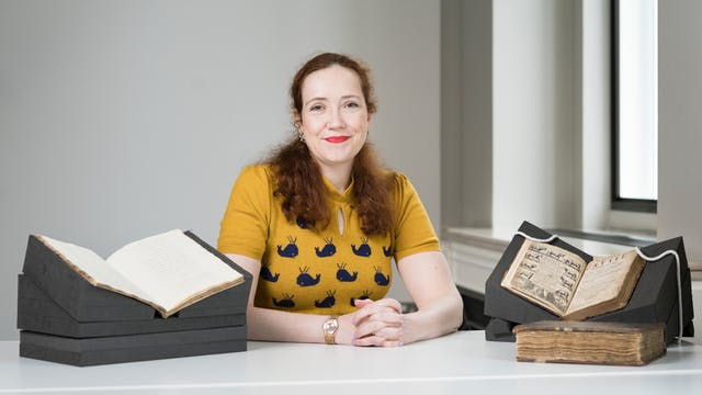Photograph of Dr  Kathleen Walker-Meikle sitting at a table in front of manuscripts from Wellcome Collection.