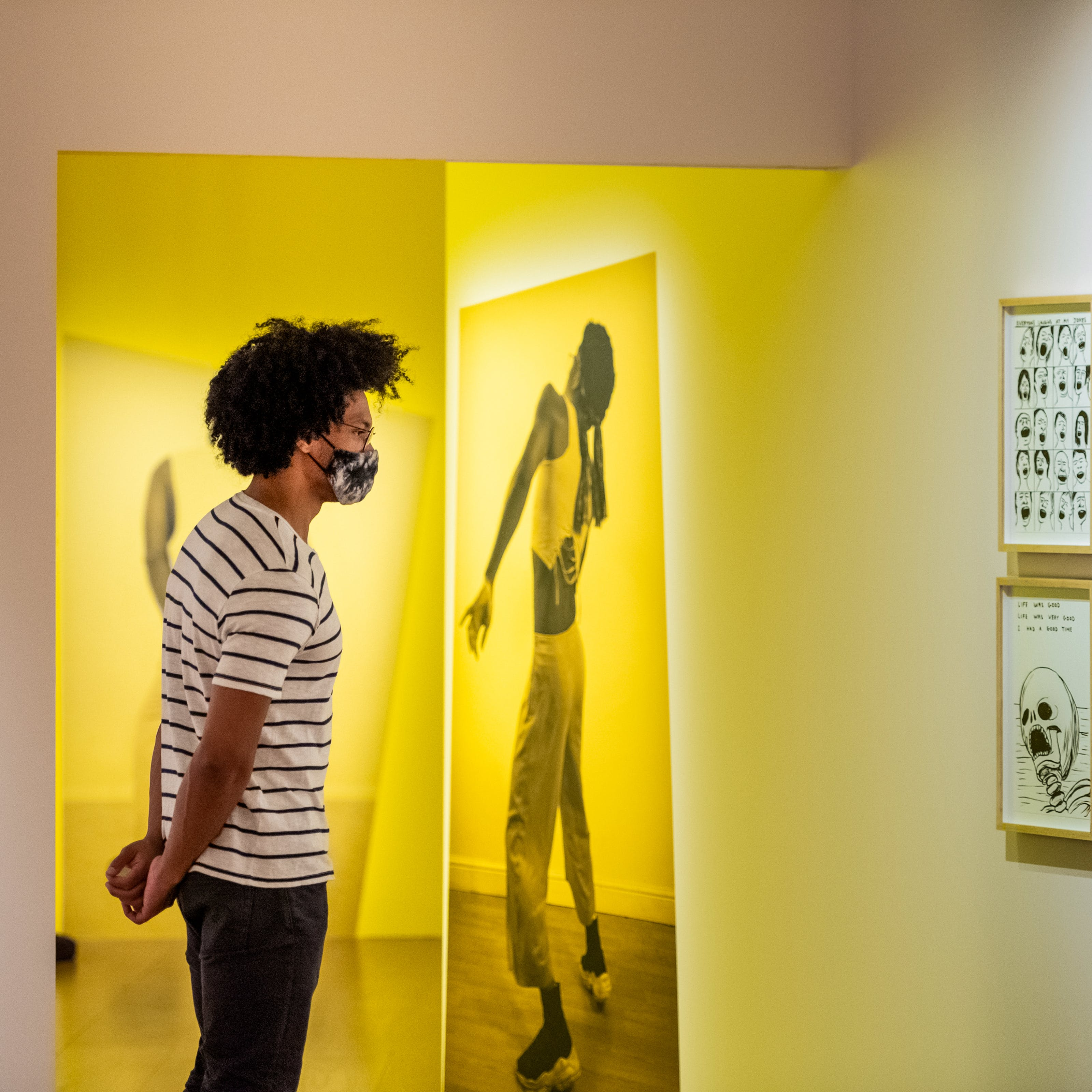 Photograph of a man wearing a face mask exploring an exhibition gallery space. He is wearing a white t-shirt with thin black horizontal stripes and jeans. His hands are clasped behind his back. The gallery around him has a warm yellow and pink tone. Directly in front of him is a large photographic print of a person in full length, frozen in a performative pose. Hung on the wall to the right is a cluster of 6 framed pen and ink drawings, 3 across by 2 high, showing in one a skull, in another a bird cage and in another a series of hands.